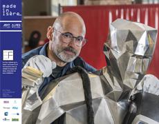 Photographie d'Eric Faure, artisan d'art voironnais avec une de ses sculptures en métal